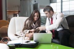 商人和女实业家在会议上与膝上型计算机和片剂 免版税库存图片