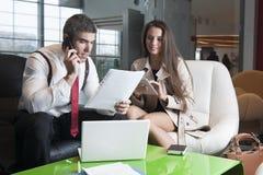 商人和女实业家在会议上与膝上型计算机和片剂 库存图片