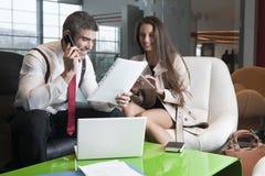 商人和女实业家在会议上与膝上型计算机和片剂 库存照片