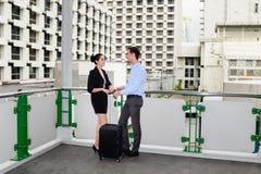 商人和女实业家在室外地方站立并且谈论与黑行李的事务 免版税库存图片