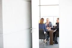 商人和女实业家在通过门户开放主义看的证券交易经纪人行情室在办公室 免版税库存图片