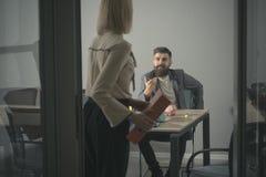 商人和女实业家工作过程的 有胡子的男人和妇女开业务会议 对秘书的上司谈话 免版税库存图片
