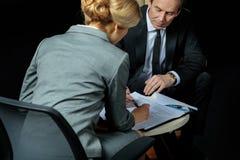 商人和女实业家签署的纸一起 库存照片