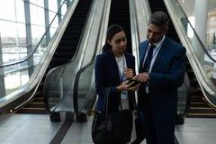 商人和女实业家谈论在手机在自动扶梯附近 免版税库存照片