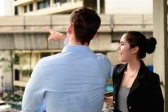 商人和女实业家谈论室外的事务,他指向手指修造 库存照片