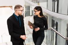 商人和女实业家谈论某事在咖啡休息期间 免版税图库摄影