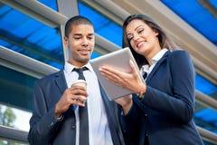 商人和妇女有片剂计算机的 免版税库存图片