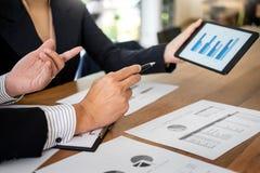 商人和妇女谈论关于在数字的财政计划 免版税库存照片