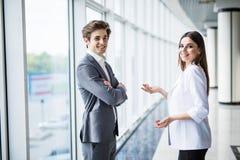 商人和妇女谈话与在大全景窗口的背景的微笑在一个现代商业中心 塑造d 免版税库存图片