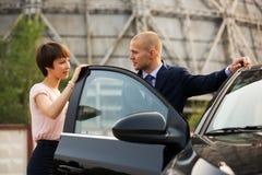 年轻商人和妇女谈话在汽车 免版税图库摄影
