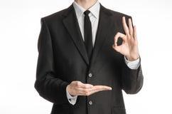 商人和姿态题目:一套黑衣服的一个人与显示与他的左手和举行的领带好标志他的在a的右手 免版税库存照片