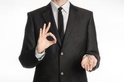 商人和姿态题目:一套黑衣服的一个人与显示与他的左手和举行的领带好标志他的在a的右手 免版税图库摄影