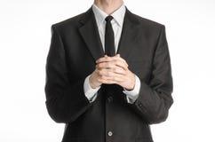 商人和姿态题目:一套黑衣服的一个人与领带折叠了他的在他前面的手和祈祷,思考的businessm 库存照片