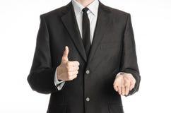 商人和姿态题目:一套黑衣服的一个人与领带显示右手赞许和拿着他的在isol的左手 免版税库存图片