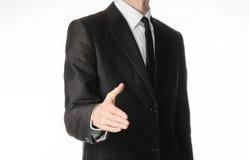 商人和姿态题目:一条黑衣服和领带的一个人在演播室提供他的手招呼隔绝在白色背景 免版税库存图片