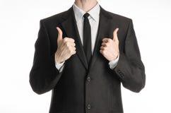 商人和姿态题目:在白色背景与领带显示两手赞许隔绝的一套黑衣服的一个人在演播室 免版税库存图片