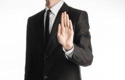 商人和姿态题目:在白色背景与领带显示中止手势隔绝的一套黑衣服的一个人在演播室 免版税库存图片