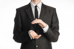 商人和姿态题目:握在前面的一条黑衣服和领带的一个人手隔绝在白色背景在演播室 图库摄影