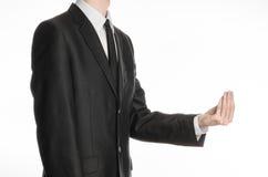 商人和姿态题目:握他的在他前面的一条黑衣服和领带的一个人手和展示在isol的少量姿态 库存图片