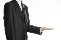 商人和姿态题目:握他的在他前面的一条黑衣服和领带的一个人手在st的白色背景隔绝了 库存图片