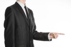 商人和姿态题目:握他的在他的食指隔绝的他和展示前面的一条黑衣服和领带的一个人手 库存图片