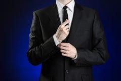 商人和姿态题目:改正夹克的一件黑衣服和白色衬衣的一个在深蓝背景的人和领带在螺柱 免版税库存照片