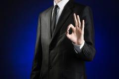 商人和姿态题目:显示在深蓝背景的一件黑衣服和白色衬衣的一个人好手标志在演播室是 免版税图库摄影