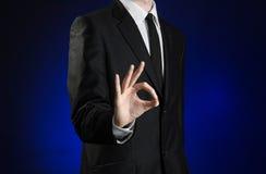 商人和姿态题目:显示在深蓝背景的一件黑衣服和白色衬衣的一个人好手标志在演播室是 库存照片