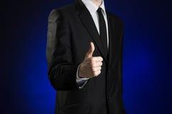 商人和姿态题目:显示在深蓝背景的一件黑衣服和白色衬衣的一个人赞许手在演播室 图库摄影
