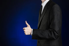商人和姿态题目:显示手势在深蓝背景的一件黑衣服和白色衬衣的一个人翘拇指我 免版税库存照片