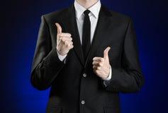 商人和姿态题目:显示手势在深蓝背景的一件黑衣服和白色衬衣的一个人翘拇指我 免版税库存图片