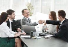 商人和投资者握手在谈判桌上 图库摄影