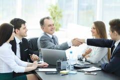 商人和投资者握手在谈判桌上 免版税图库摄影