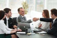 商人和投资者握手在谈判桌上 库存照片