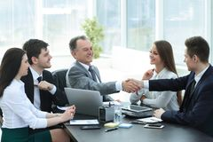 商人和投资者握手在谈判桌上 库存图片