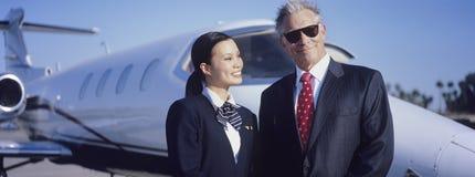 商人和空中小姐在航空器前面 免版税库存图片