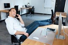 商人和谈话坐手机在办公室 免版税图库摄影