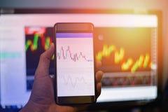 商人商业交换关于流动屏幕/外汇图的委员会数据注标在智能手机的交换 库存图片