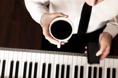 年轻商人喝在钢琴前面的咖啡与电话 库存照片