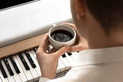 年轻商人喝在钢琴前面的咖啡 免版税库存照片
