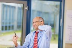 商人固定的单元电话,当遭受脖子痛时 免版税库存照片