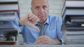 商人图象在认为的屋子里做烦恶在标志下的姿态拇指 免版税库存照片