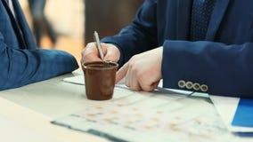 商人图画在习字簿的企业图在有办公室工具和咖啡的桌面上 影视素材