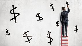 商人在一个红色活梯站立并且画在白色墙壁上的黑美元的符号 免版税库存图片