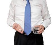 商人在一只手和水杯子上的拿着一个药片在另一只手上 库存图片