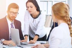 商人在一次会议上在办公室 集中于指向入膝上型计算机的妇女 免版税库存图片