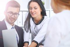商人在一次会议上在办公室 集中于指向入膝上型计算机的妇女 免版税库存照片