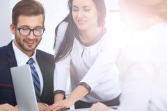 商人在一次会议上在办公室 集中于指向入膝上型计算机的妇女 库存照片