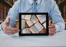 商人在与片剂陈列开放书的桌上反对模糊的书架 免版税图库摄影