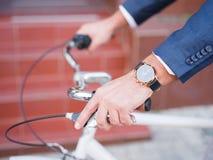 商人在他的在街道特写镜头时钟的白色自行车乘坐 库存照片
